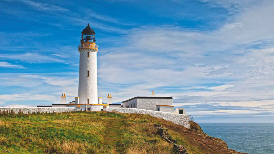 White lighthouse at Mull of Galloway overlooking calm summer seas