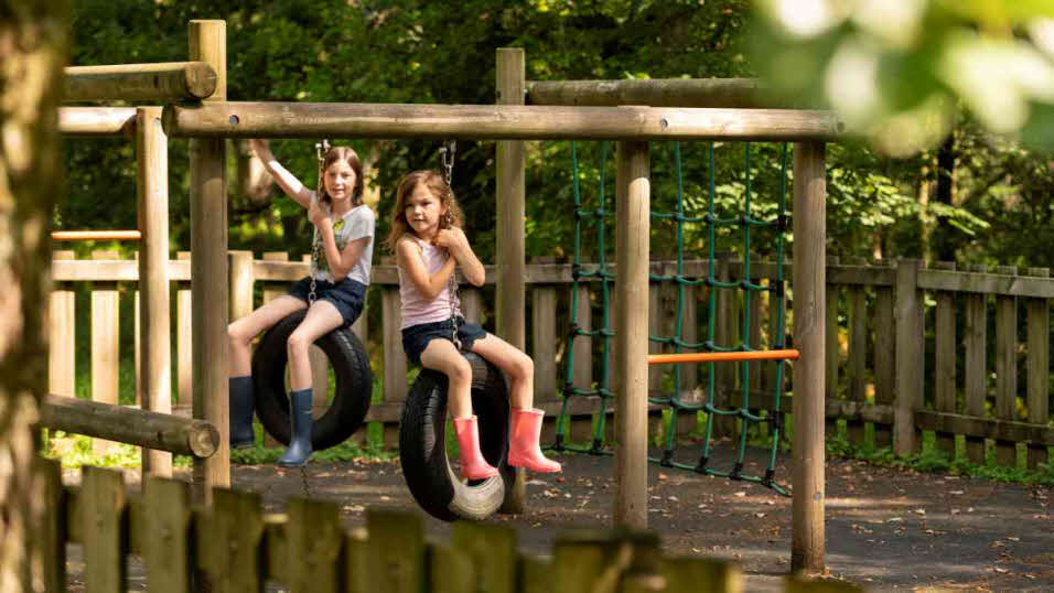 Children playing on tyre swings in Coniston Park Coppice