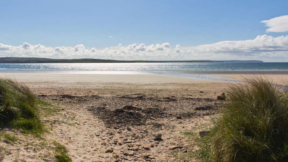 Sand dunes and calm waters at Dunnet Bay beach