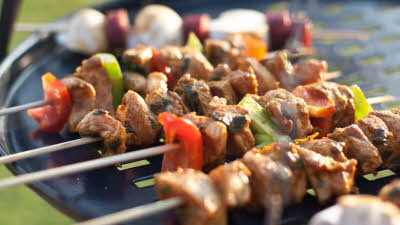 Pork kebabs with peppers cooking on a black barbecue