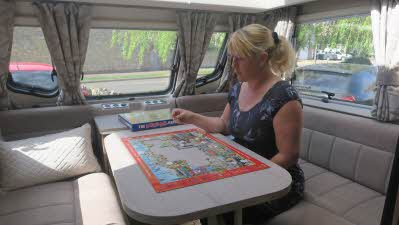 Writer Sammy Faircloth works on a jigsaw on a table inside her caravan
