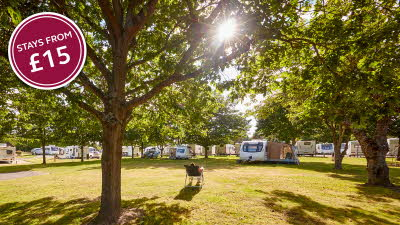 A man sits in his chair and enjoys the sunshine at Bearstead Club Site