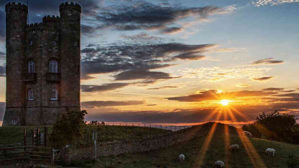Sun setting on Broadway Tower and field of sheep