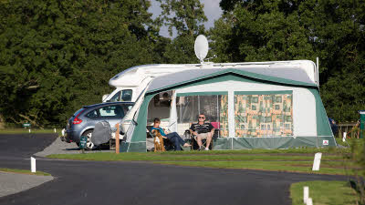 Motorhome with awning and two campers in camper chairs