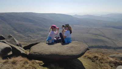 Two children enjoy the views from the top of Kinder Scout in the Peak District National Park