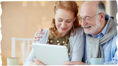 couple using tablet wearing headphones
