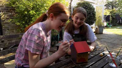 Two girls painting a birdbox on a patio in a back garden.