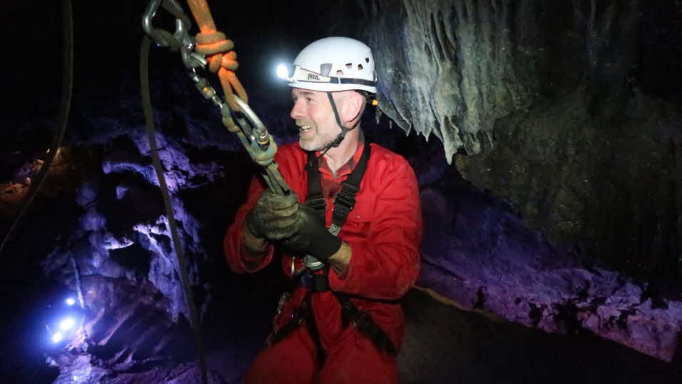 Man exploring cave wearing harness and safety gear