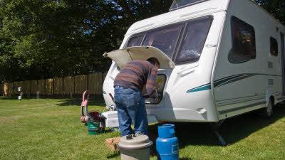 Man setting caravan ready for holiday