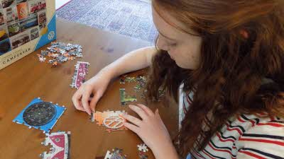 A girl pieces together a jigsaw of several campervans