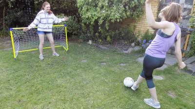 Two girls playing football in the back garden with small goal and trees behind.