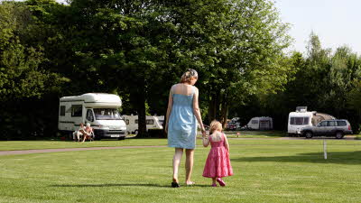 Mother and daughter walking on grass at Cirencester Park