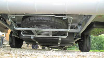 the underside of a motorhome showing the spare tyre
