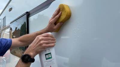 Cleaning the caravan's sidewall with sponge and Autoglym product