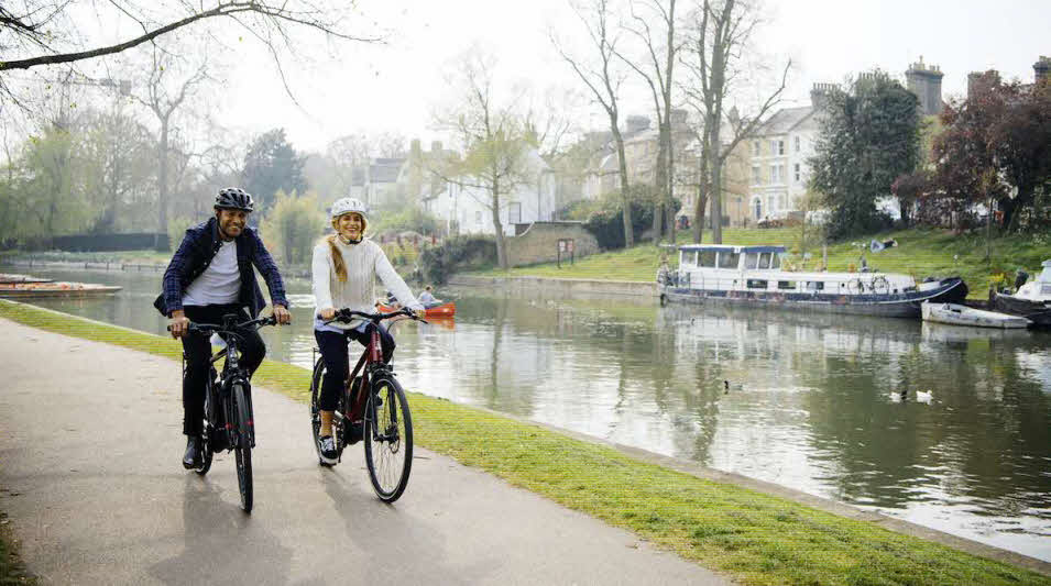 Couple riding electric bikes by the river