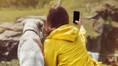 Girl holding out her mobile phone to take a selfie with her dog on a grassy bank