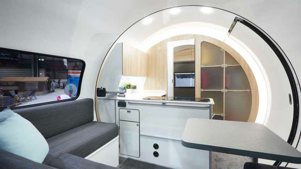 Modern interior of a new caravan with hidden storage and table