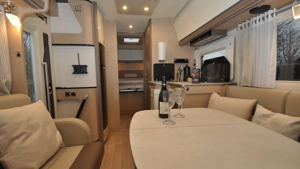Spacious M96 motorhome interior with table, seating, kitchen and storage