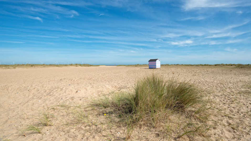 Small beach hut among sands and grassy patches at Great Yarmouth beach
