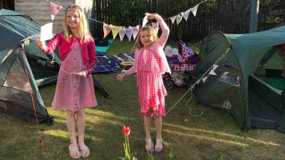 Two girls in a garden stand in front of bunting and tents during the Big Little Tent Festival