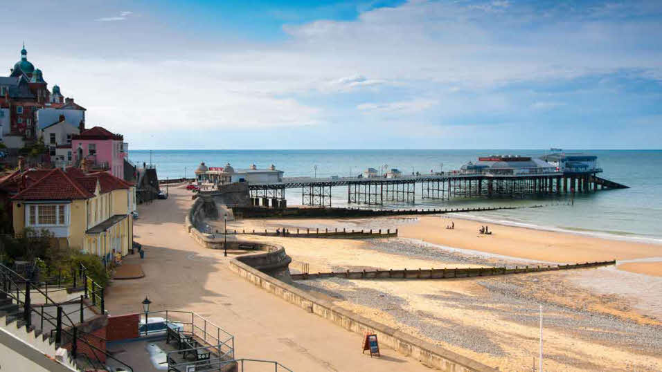 Sunny day at quiet and sandy Cromer Beach and Cromer Pier in Norfolk