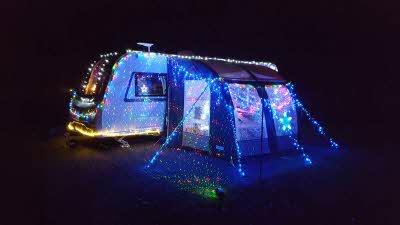 Caravan and awning covered in Christmas lights