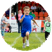 young boy in blue t-shirt running in a race