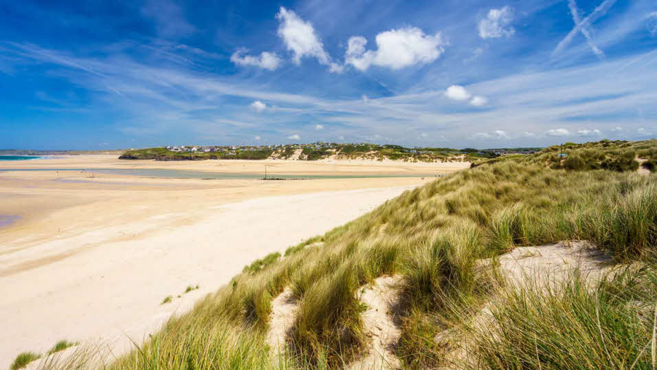 Grassy sand dunes at Porthkidney Beach, with clear blue skies and low tide