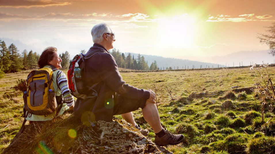 Elderly couple sitting on a rock in a wide open field