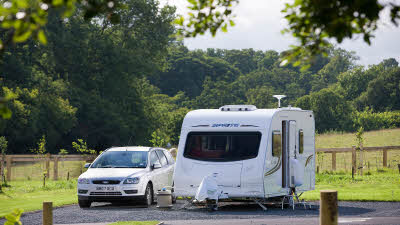 Car and caravan by fenced field