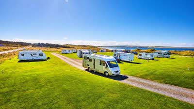 Dunnet Bay campsite with caravans and motorhomes parked on cut grass overlooking bay